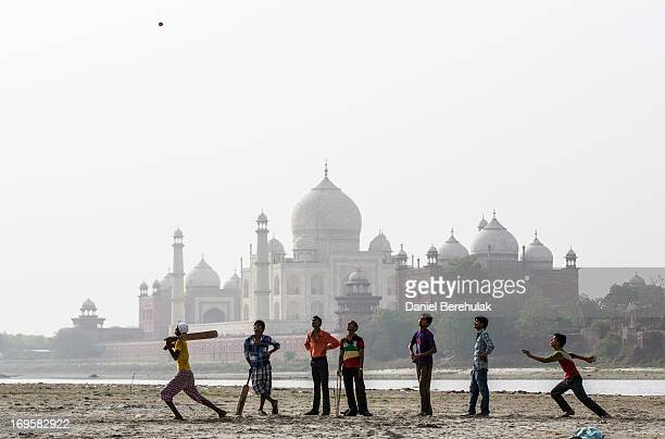 Indian boys play cricket on the banks of the Yamuna river as the Taj Mahal is seen in the distance on May 28 2013 in Agra India Completed in 1643 the...