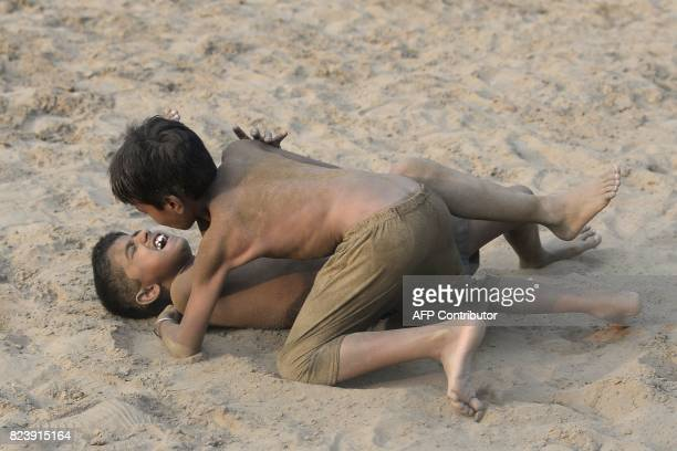 Indian boys practice 'Kushti' at a village near Jalandhar on July 28 2017 Kushti traditional wrestling is popular across the subcontinent and was...
