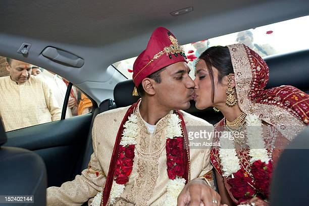 indian bride and groom in traditional clothing kissing in car - kissing stock pictures, royalty-free photos & images