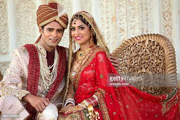 indian bride and groom in traditional wedding dress sitting on a couch - hinduism bildbanksfoton och bilder