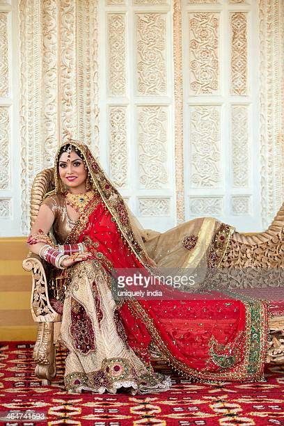 Indian bride in traditional wedding dress sitting on a couch