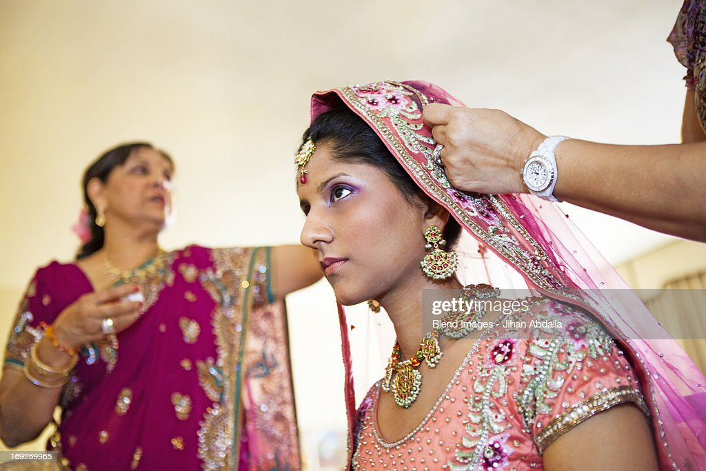 Indian bride wearing colorful fabrics and jewelry : Stock Photo