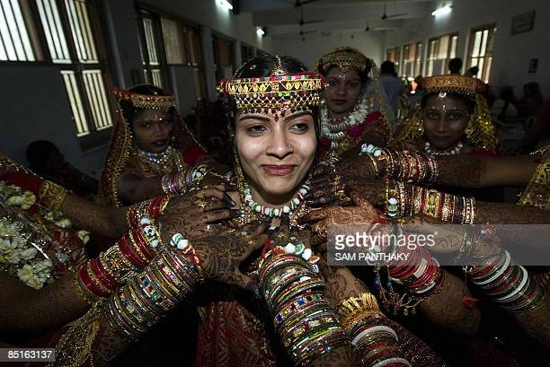 Indian brides wear traditional wedding dress as they prepare to participate in a mass marriage ceremony at Bavla some 35kms from Ahmedabad on...
