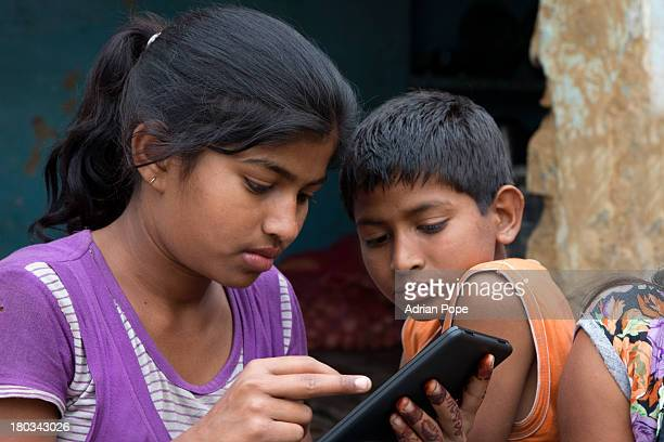Indian brother and sister using tablet device