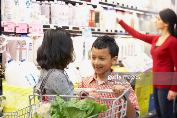 Indian brother pushing sister in shopping cart