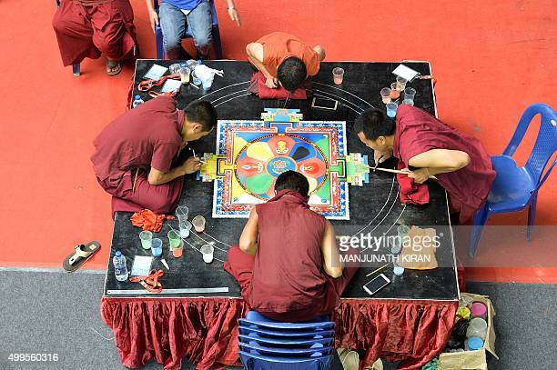 TOPSHOT Indian Buddhist monks draw a mandala with coloured sand during a Buddhist Festival in Bangalore on December 2 2015 AFP PHOTO/MANJUNATH KIRAN...