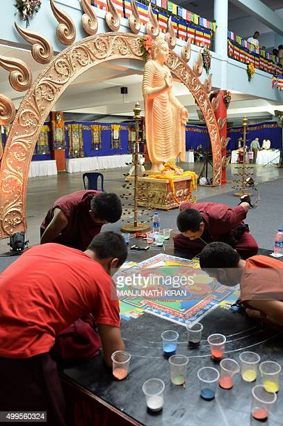 Indian Buddhist monks draw a mandala with coloured sand during a Buddhist Festival in Bangalore on December 2 2015 AFP PHOTO/Manjunath KIRAN / AFP /...
