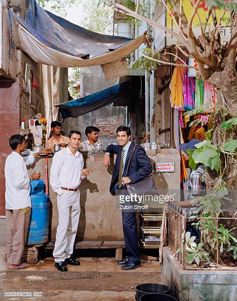 Indian business men drinking tea at stall, full length