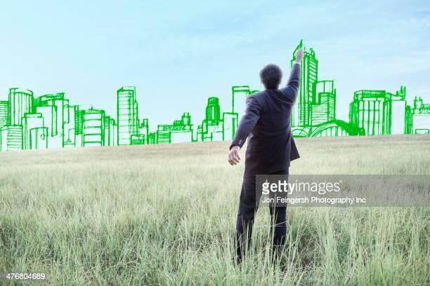 Indian businessman drawing buildings on sky