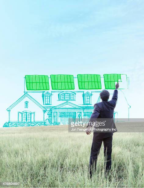 Indian businessman drawing solar panels on home
