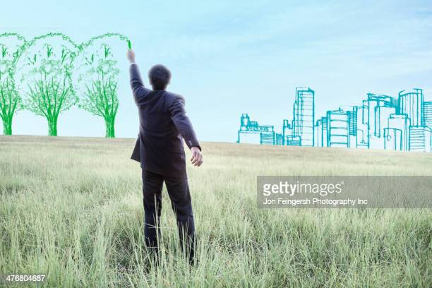 indian businessman drawing trees on sky - responsible business stock photos and pictures