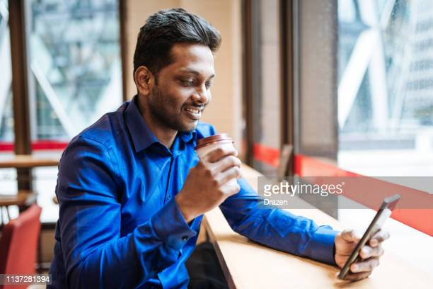 Indian businessman enjoys coffee break in UK and using phone