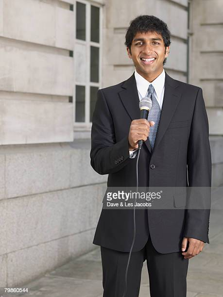 Indian businessman holding microphone