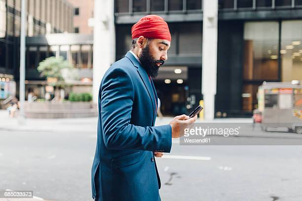 Indian businessman in Manhattan using smartphone, walking in the street