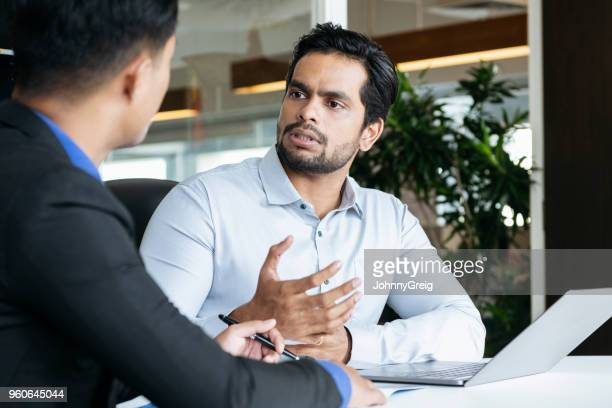 Indian businessman listening and gesturing