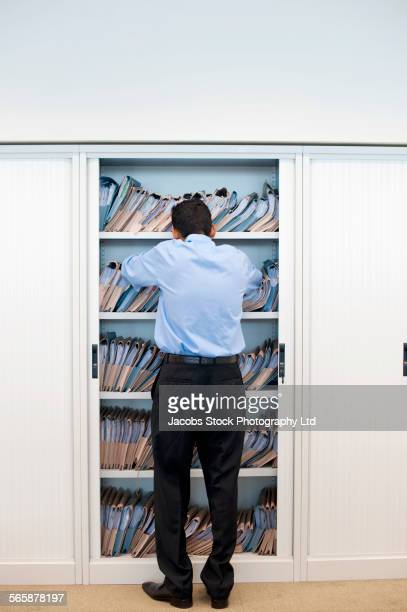 Indian businessman looking at files in cabinet