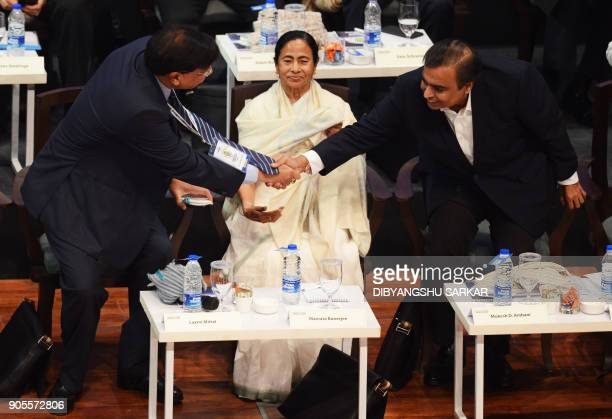 Indian businessman Mukesh Ambani shakes hand with businessman Lakshmi Mittal as chief minister of the eastern Indian state of West Bengal Mamata...
