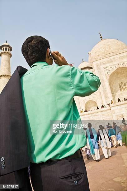 Indian businessman on cell phone visiting Taj Mahal