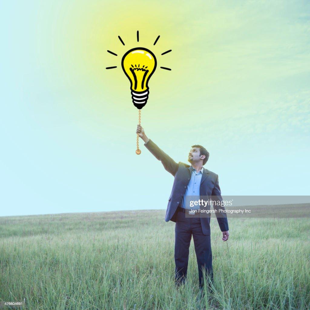 Indian businessman pulling chain on light bulb illustration : Stock Photo