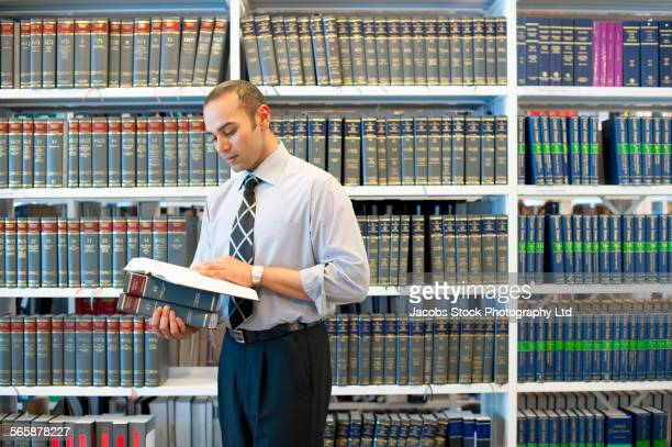 indian businessman reading book in law library - law stock pictures, royalty-free photos & images