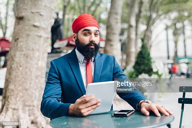 Indian businessman sitting in Manhattan, using digital tablet