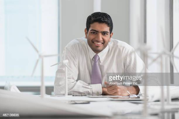 Indian businessman smiling with wind turbine models