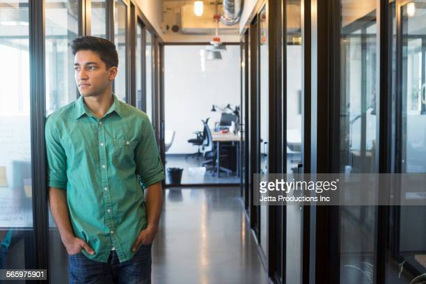 Indian businessman standing in office hallway