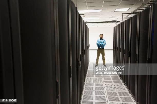indian businessman standing in server room - beschützer stock-fotos und bilder