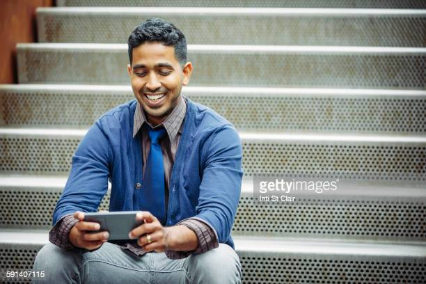 indian businessman using cell phone on steps - indian subcontinent ethnicity stock pictures, royalty-free photos & images