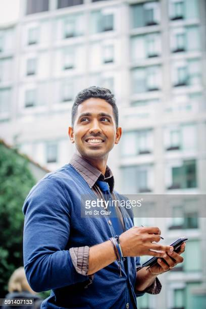 Indian businessman using cell phone outdoors