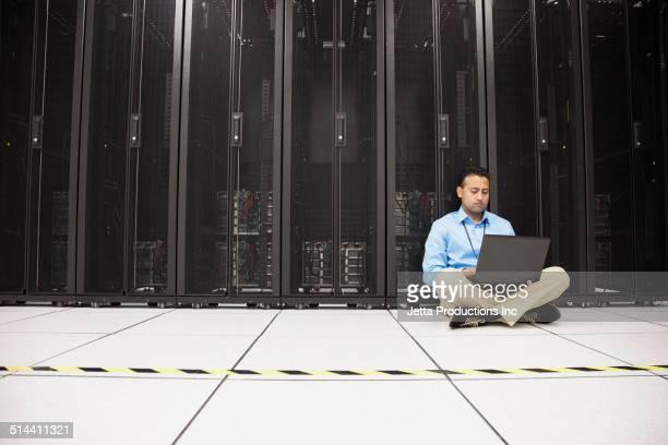 Indian businessman using laptop in server room