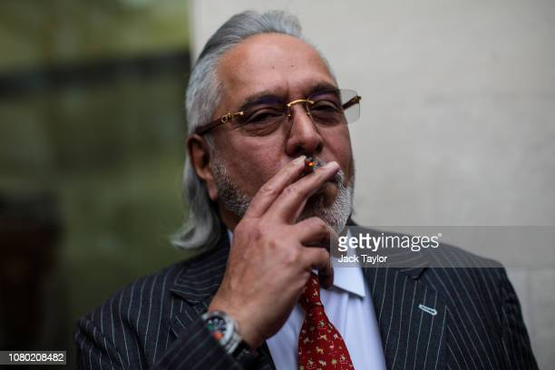 Indian businessman Vijay Mallya smokes during a break in his extradition ruling at Westminster Magistrates Court on December 10 2018 in London...