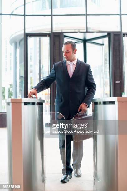Indian businessman walking through turnstile