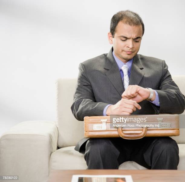 Indian businessman with briefcase looking at watch on sofa