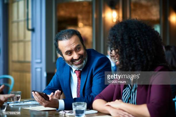indian businessman with phone looking at colleague and smiling - formal portrait fotografías e imágenes de stock