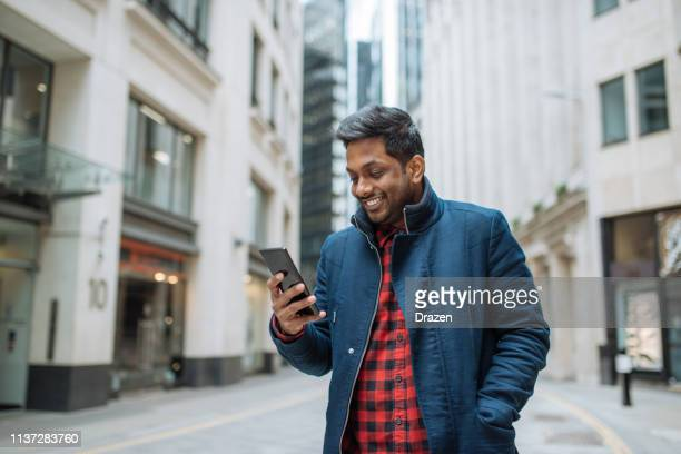 Indian businessman with smart phone, using mobile app.