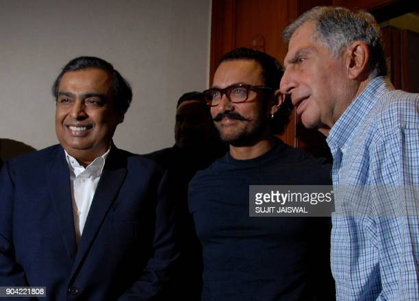 Indian businessmen Mukesh Ambani and Ratan Tata and Bollywood actor Aamir Khan pose for a photograph during a promotional event in Mumbai on January...