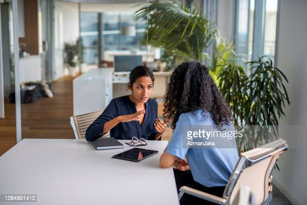 indian businesswoman explaining her situation to her coworker - complaining stock pictures, royalty-free photos & images