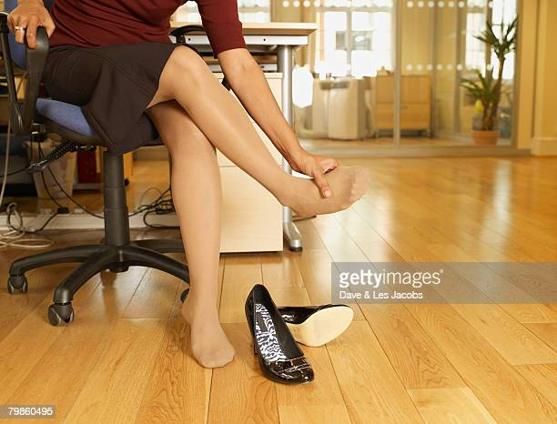 indian businesswoman rubbing foot - stockings no shoes stock photos and pictures