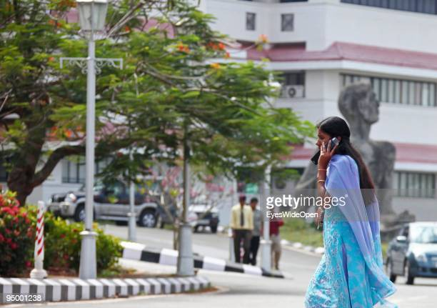 Indian businesswoman with a mobile phone at the center of technology in Kerala called technopark where highly educated women and men working at more...