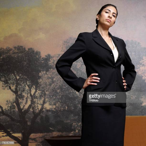 Indian businesswoman with hands on hips indoors