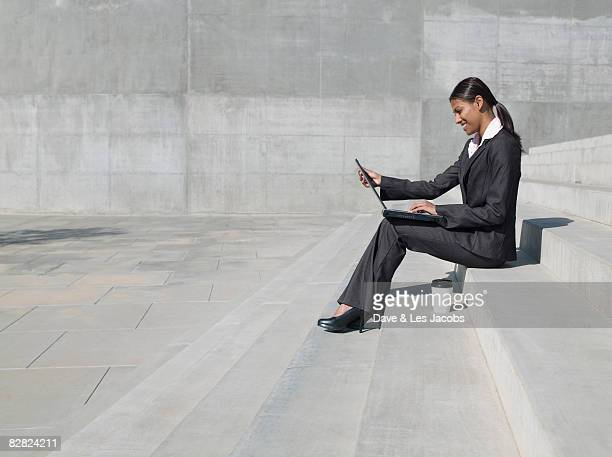 Indian businesswoman working on laptop outdoors