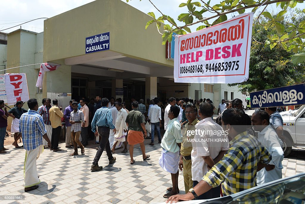 Indian Bystanders And Relatives Gather Near A Banner Announcing Help Desk For The Queries Of Injured Or Deceased Victims Puttingal