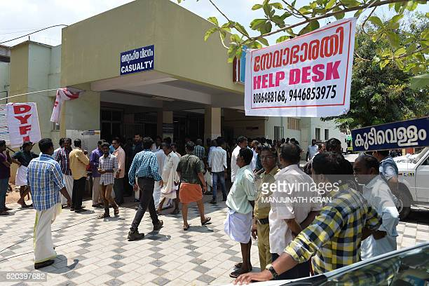 Indian bystanders and relatives gather near a banner announcing a help desk for the queries of relatives of injured or deceased victims of the...