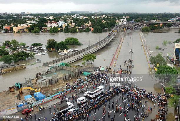 Indian bystanders and travellers gather as floodwaters lap at the end of a highway in Chennai on December 2 2015 India has deployed troops to Tamil...