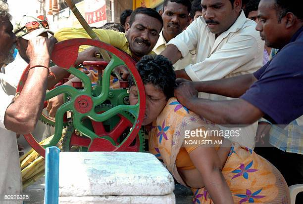 Indian bystanders attempt to free a woman whose saree became entwined in the workings of a mobile sugarcane machine at her roadside shop in Hyderabad...
