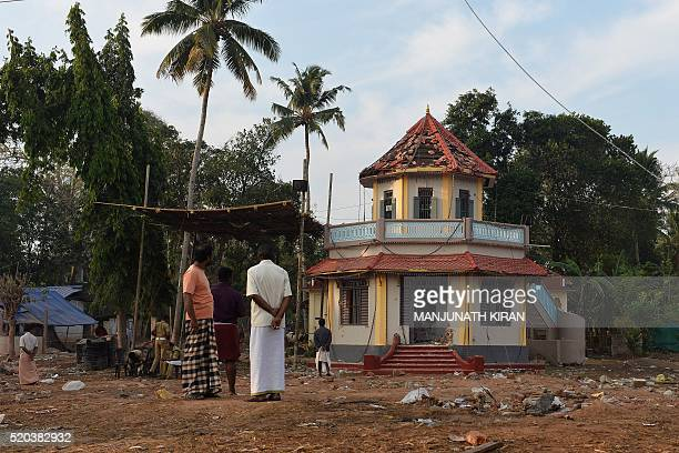 Indian bystanders gather in front of a damaged building at The Puttingal Devi Temple in Paravur some 60kms northwest of Thiruvananthapuram on April...
