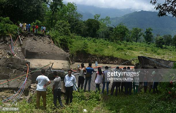Indian bystanders look at a damaged bridge in the village of Garidhura some 35kms from Siliguri on July 1 after landslides struck the eastern state...