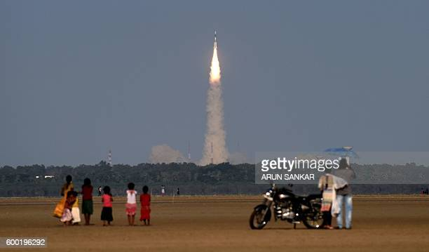TOPSHOT Indian bystanders look on as Space Research Organisation's satellite INSAT3DR on board the Geosynchronous Satellite Launch Vehicle launches...