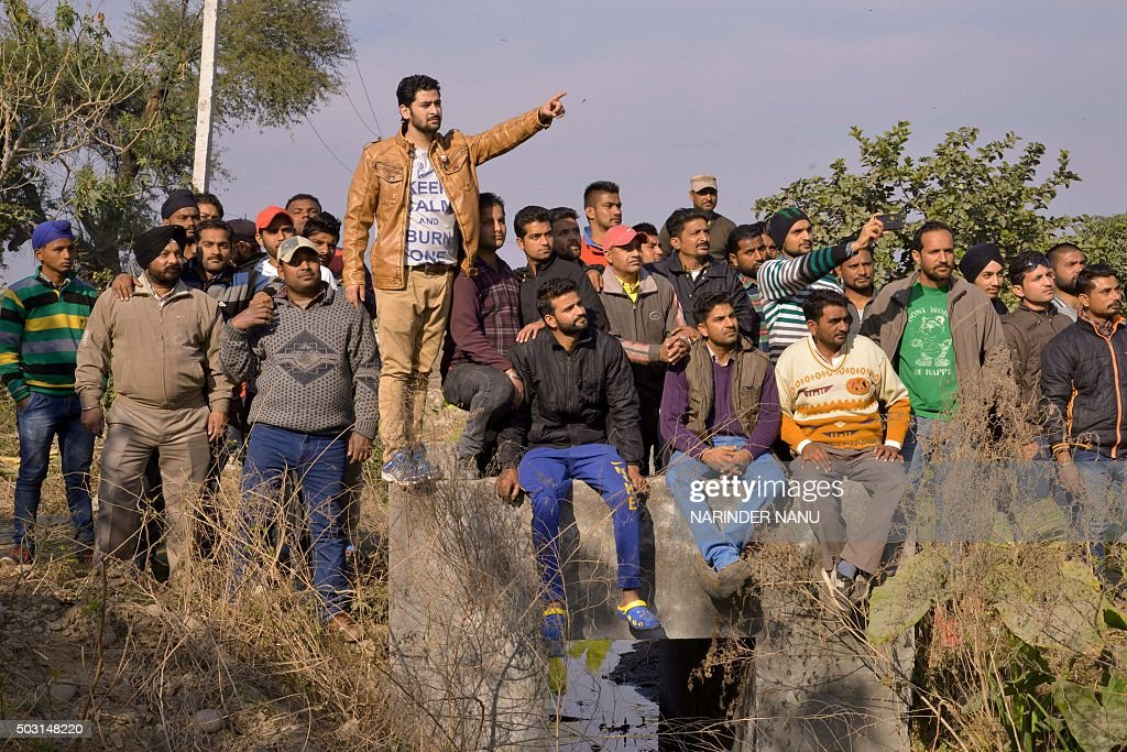 Indian bystanders look on from outside an airforce base in Pathankot on January 2 during an ongoing attack on the base in the northern Indian state...